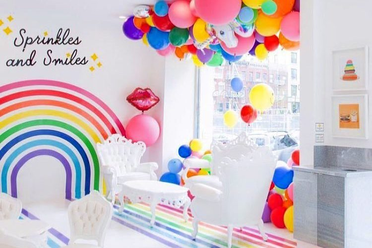 A photo of the interior of the Flour Shop storefront in NYC. It is full of balloons and rainbows.