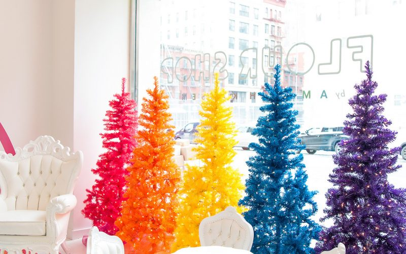 Another view of the Flour Shop storefront in New York City. It features several rainbow colored artificial trees.