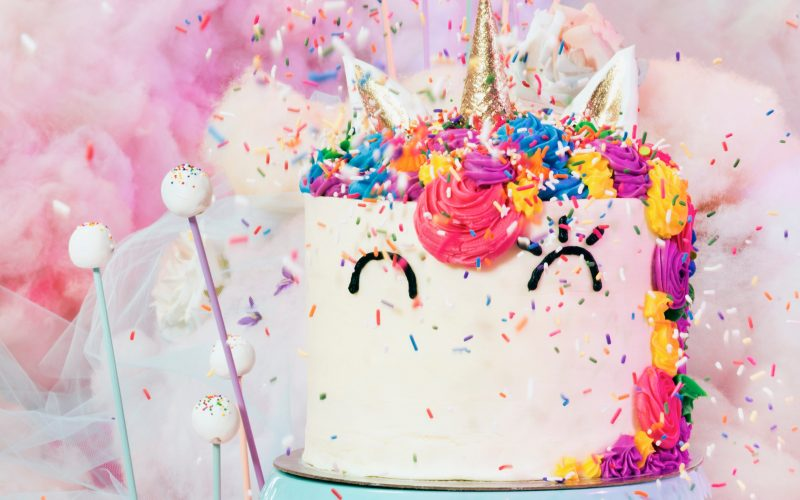 A rainbow colored unicorn themed cake with a gold unicorn horn on top.