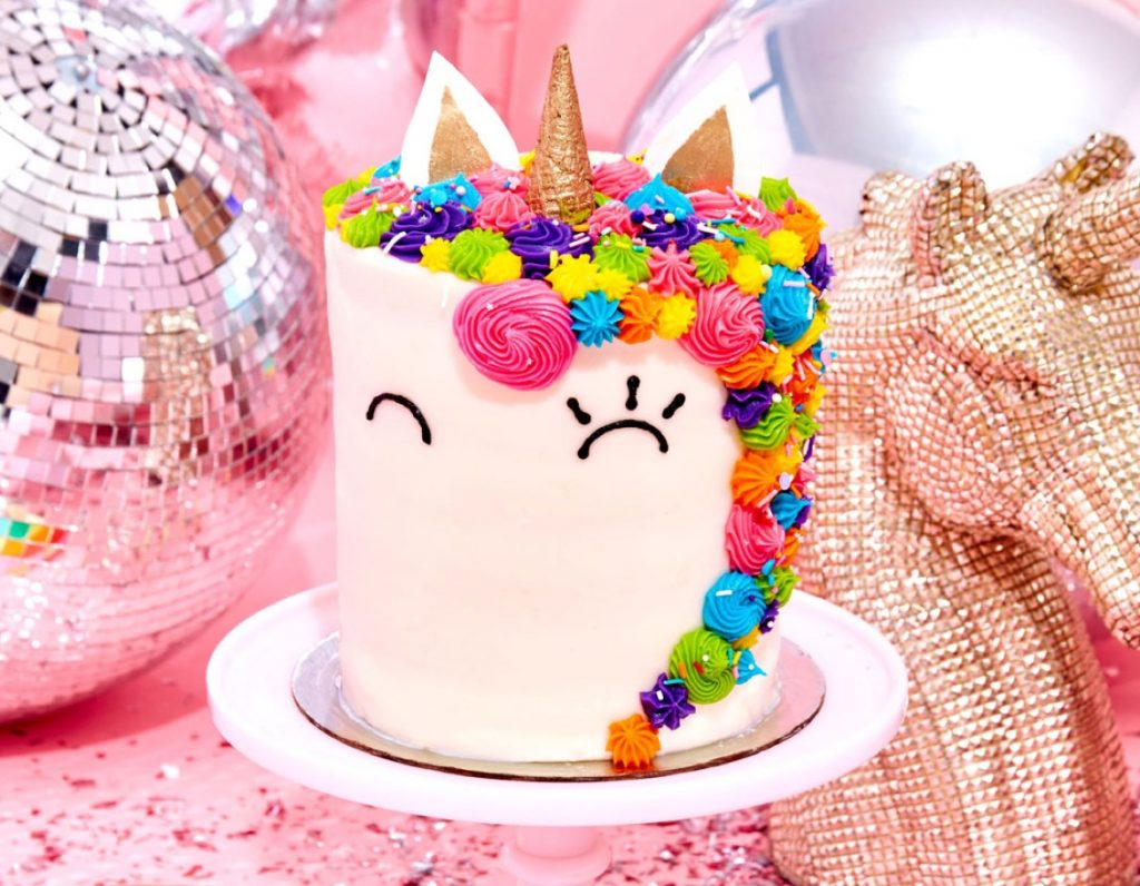 Unicorn styled cake on a pink tablecloth beside a shiny disco ball.
